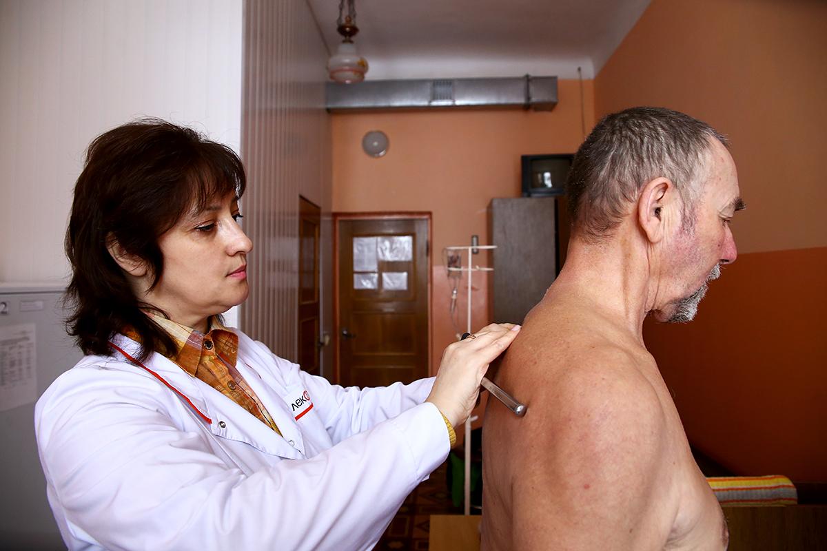 Врач-невролог, заведующий неврологическим отделением Алла Костюк проводит осмотр пациента.