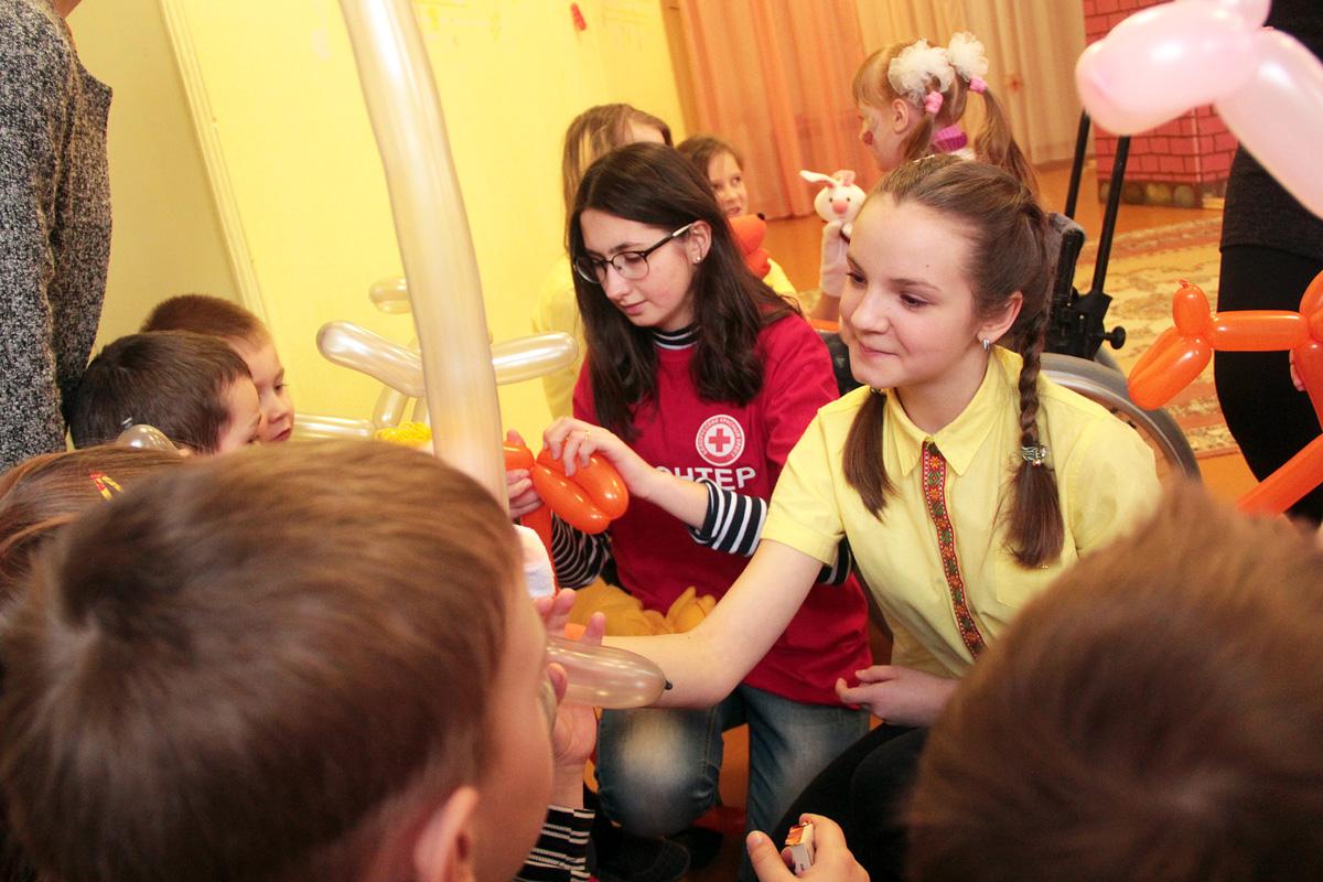 Волонтеры раздают детям поделки из воздушных шаров.
