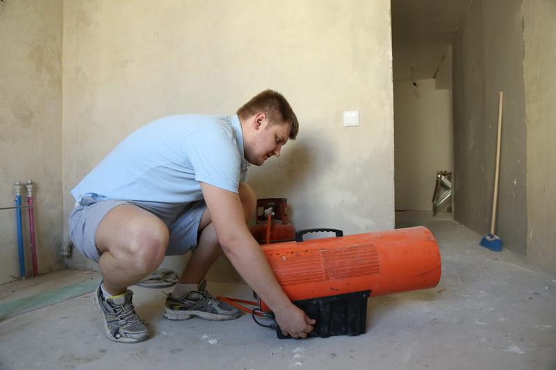 Антон  Юрчик включает «пушку» для нагрева потолочного полотна.  За три минуты аппарат нагревает воздух до +90 градусов.  фото: Александр КОРОБ