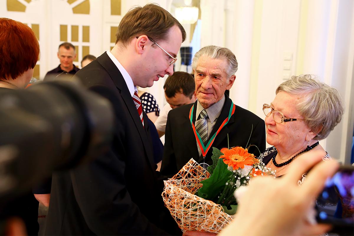 Заместитель председателя Барановичского горисполкома Алексей Гарбуз поздравляет семью Рычихиных с золотой свадьбой.