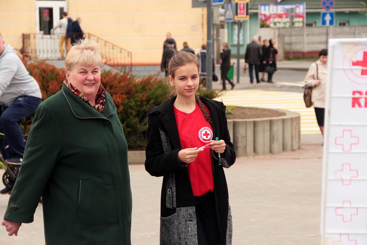Волонтеры приглашают прогуливающихся по площади горожан принять участие в лотерее.