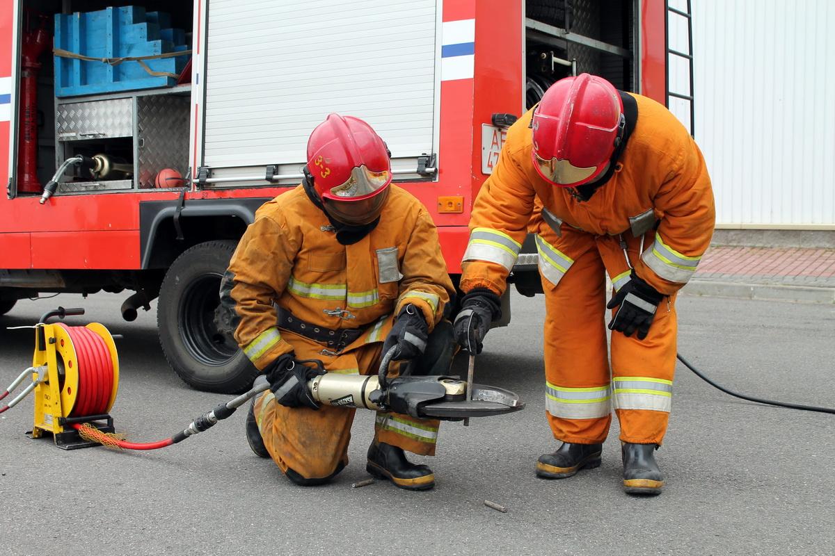 Сотрудники МЧС показывают, как гидравлические ножницы перекусывают металлический прут.