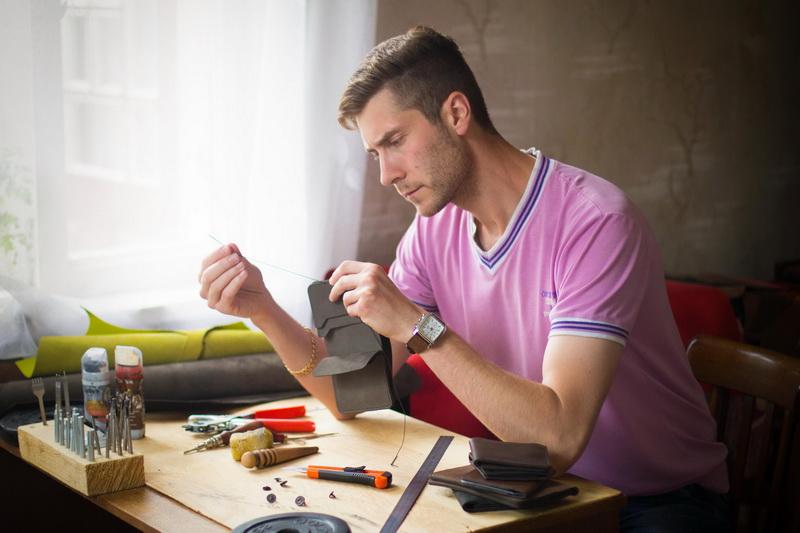 Василий Авицюк раскраивает кожу для нового кошелька. На создание такого изделия у него уходит около трех дней. Фото: Личный архив
