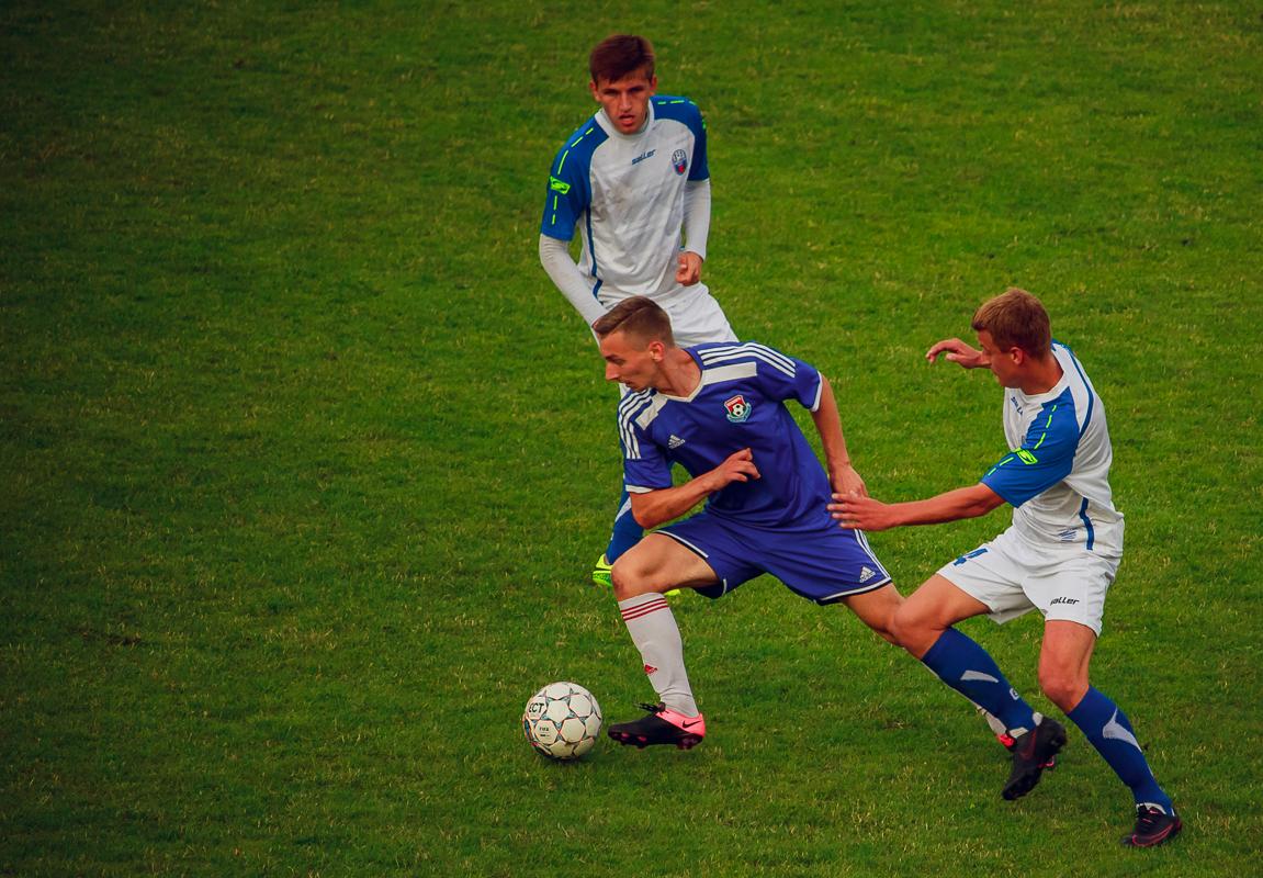 Антон Зеленевский (с мячом) против двух соперников.