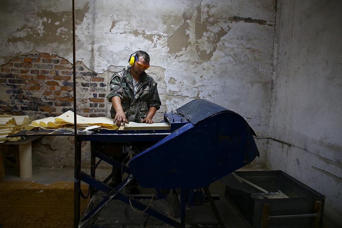 Сергей Ивановский работает на станке, который рубит шпон на тонкие детали, в дальнейшем из которых делают корзинки.