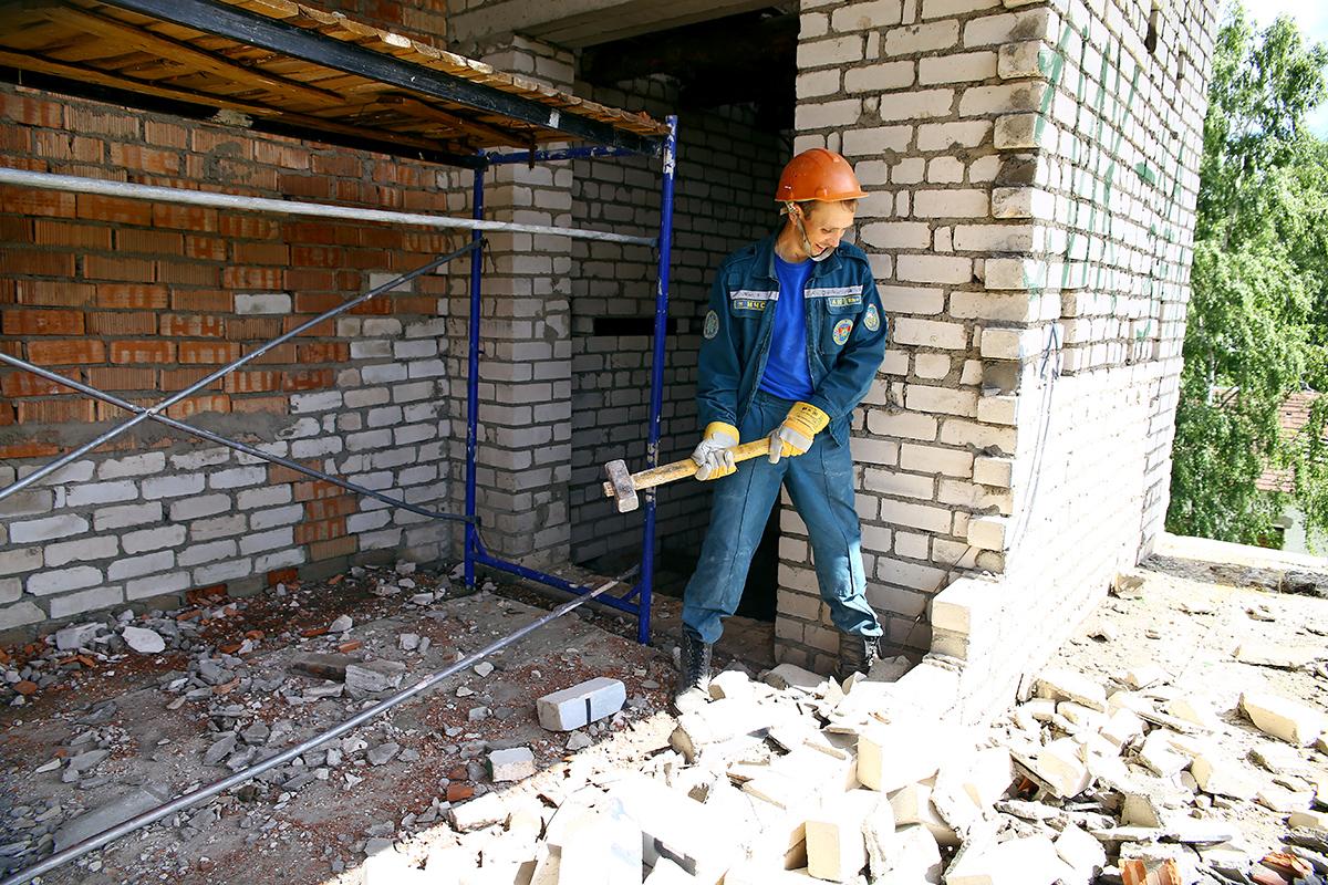 Сотрудник МЧС ломает кирпичную стену.