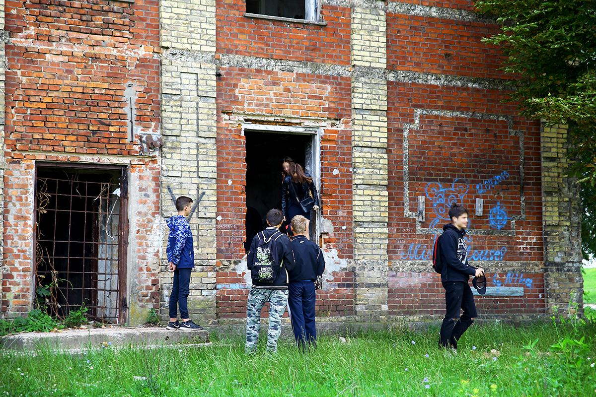 Подростки гуляют по территории заброшенного здания.