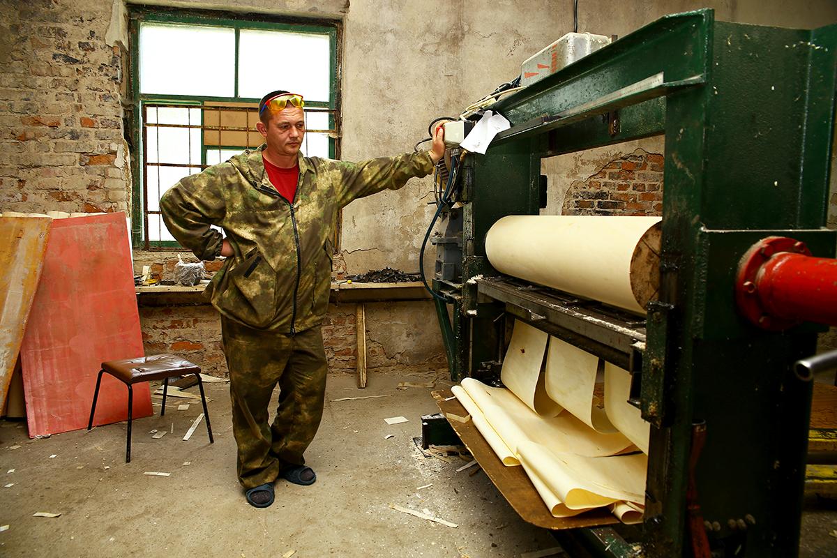 Александр Безмен работает на станке, который лущит брус на шпон.