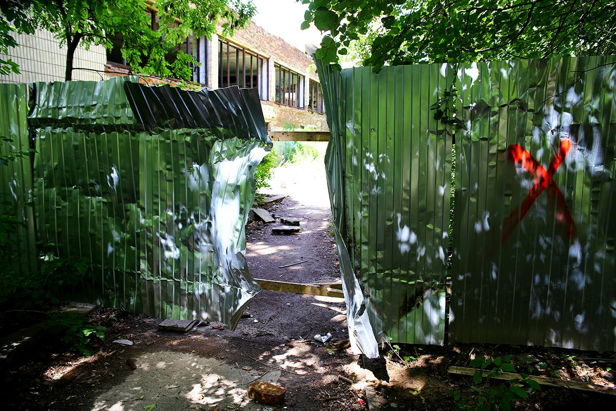 Дыра в заборе, через которую легко попасть на территорию здания.