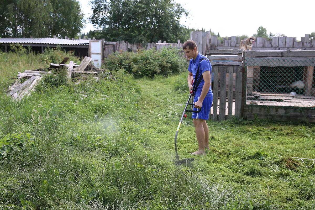 Андрей Тристень косит траву возле вольеров.