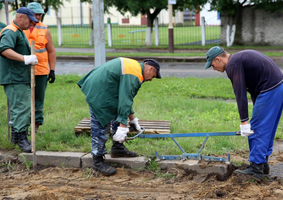 Рабочие УКРСП «Барановичиремстрой»   демонтируют тротуарный бордюр.