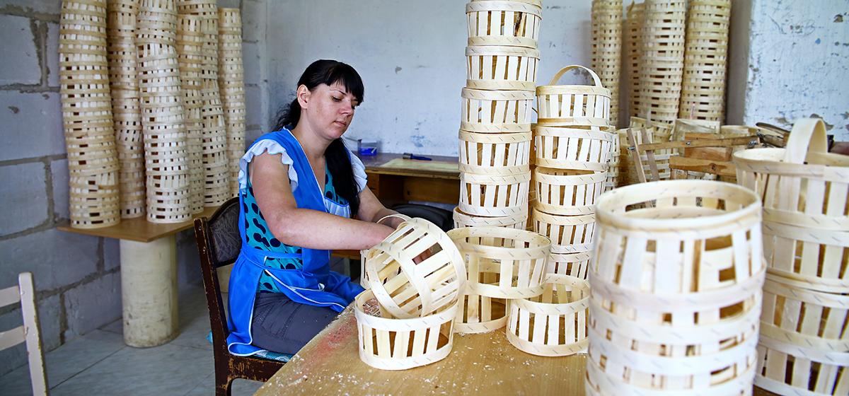 Работница предприятия Алина Синькевич выполняет одну из операций: крепит ручку к корзинке. Фото:Евгений ТИХАНОВИЧ