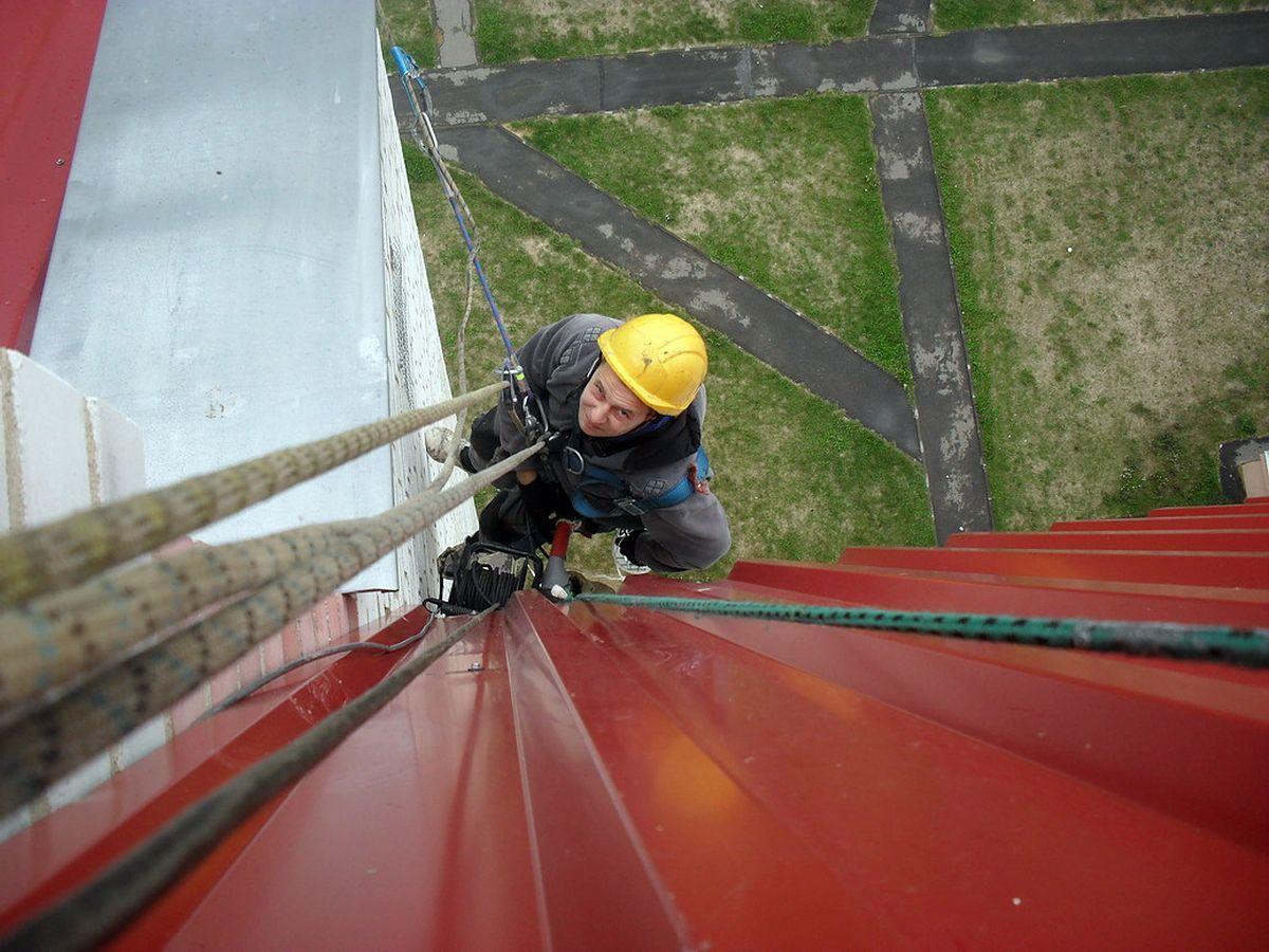 Андрей Викторов выполняет монтаж сетки в окнах на высоте 35 метров. Фото: Личный архив