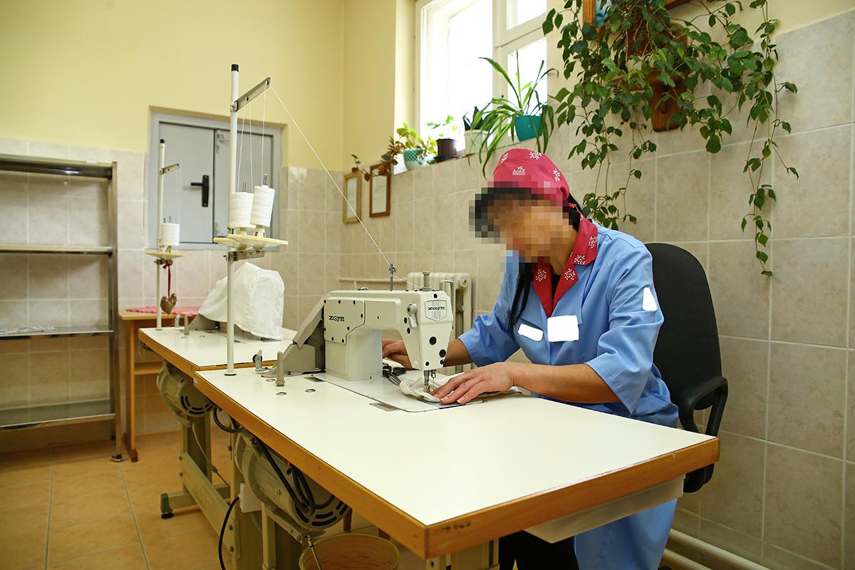 Осужденная работает за швейной машинкой.