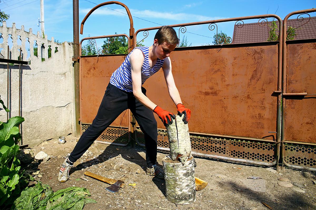 Сын Николая Черноуса Андрей колет дрова для протапливания печки, в которой активист будет выпекать хлеб.