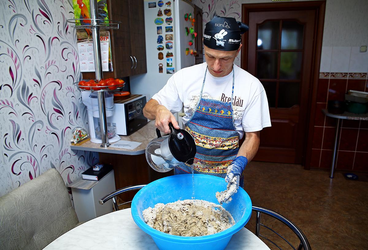 Николай Черноус замешивает тесто.