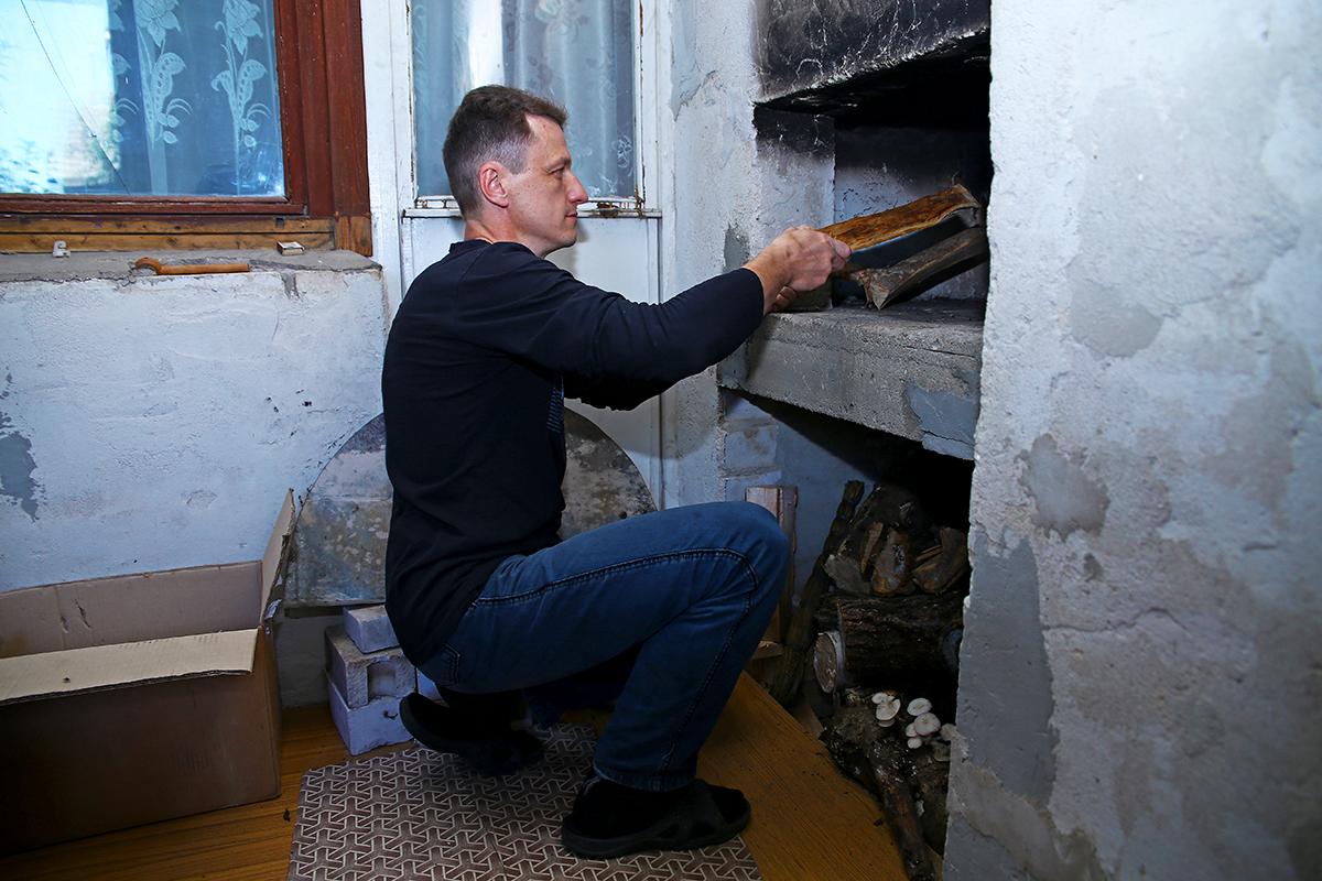 Николай подбрасывает дрова в печь.