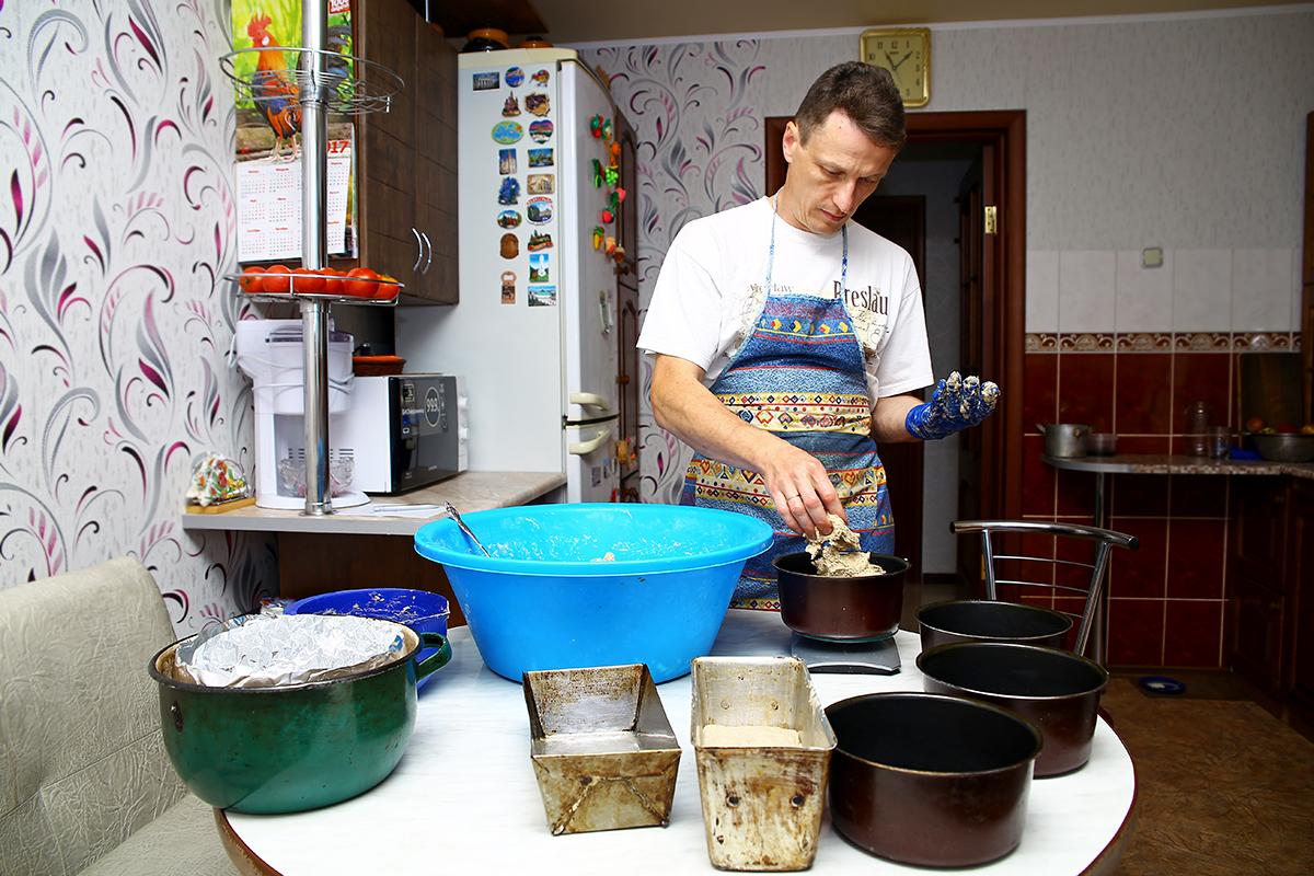 Активист раскладывает тесто в формы.
