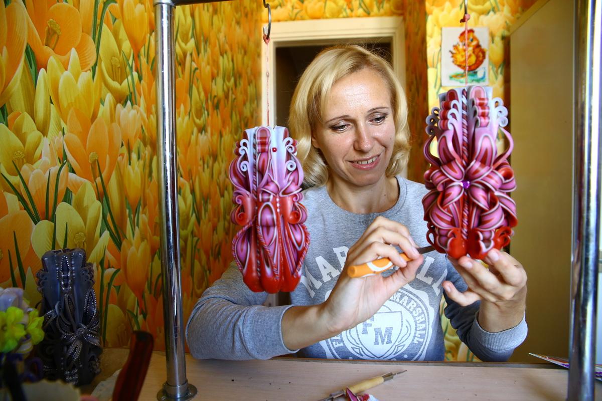 Мастер свечного дела Наталья Адамчук декорирует готовую свечу. На создание одной такой свечи может уйти до 12 часов. Фото: Евгений ТИХАНОВИЧ
