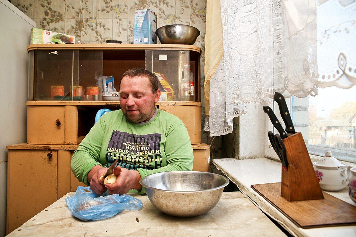 Глава семьи чистит картошку.