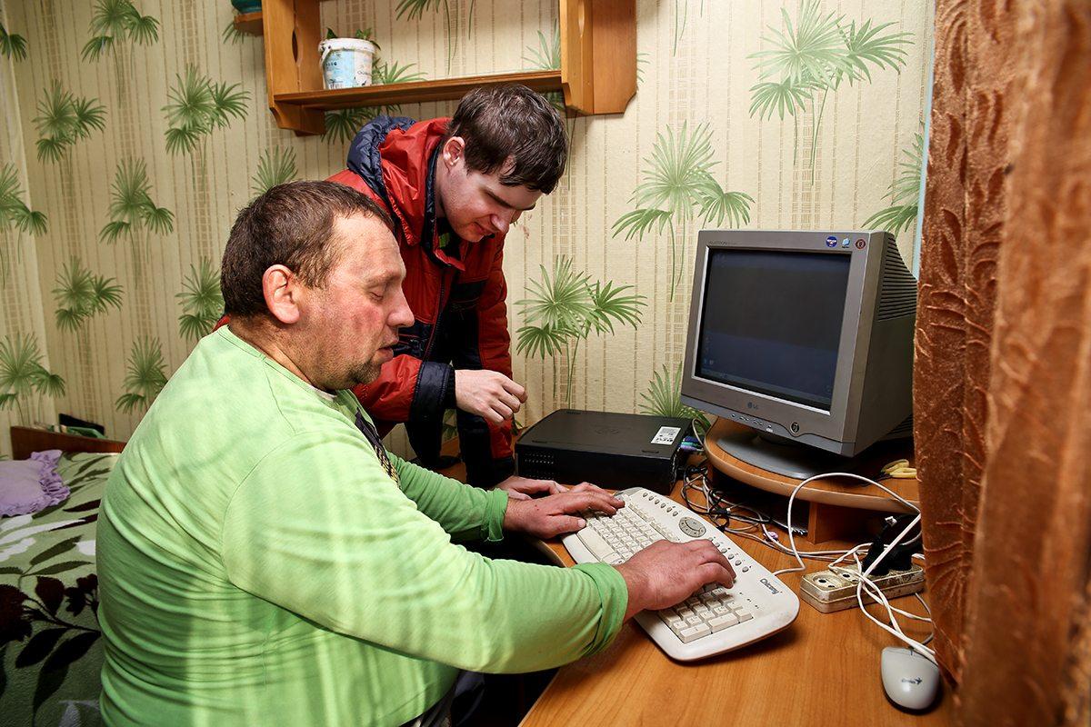 Дмитрий из «Белорусского общества инвалидов» обучает Анатолия пользоваться специальным компьютером для слепых.