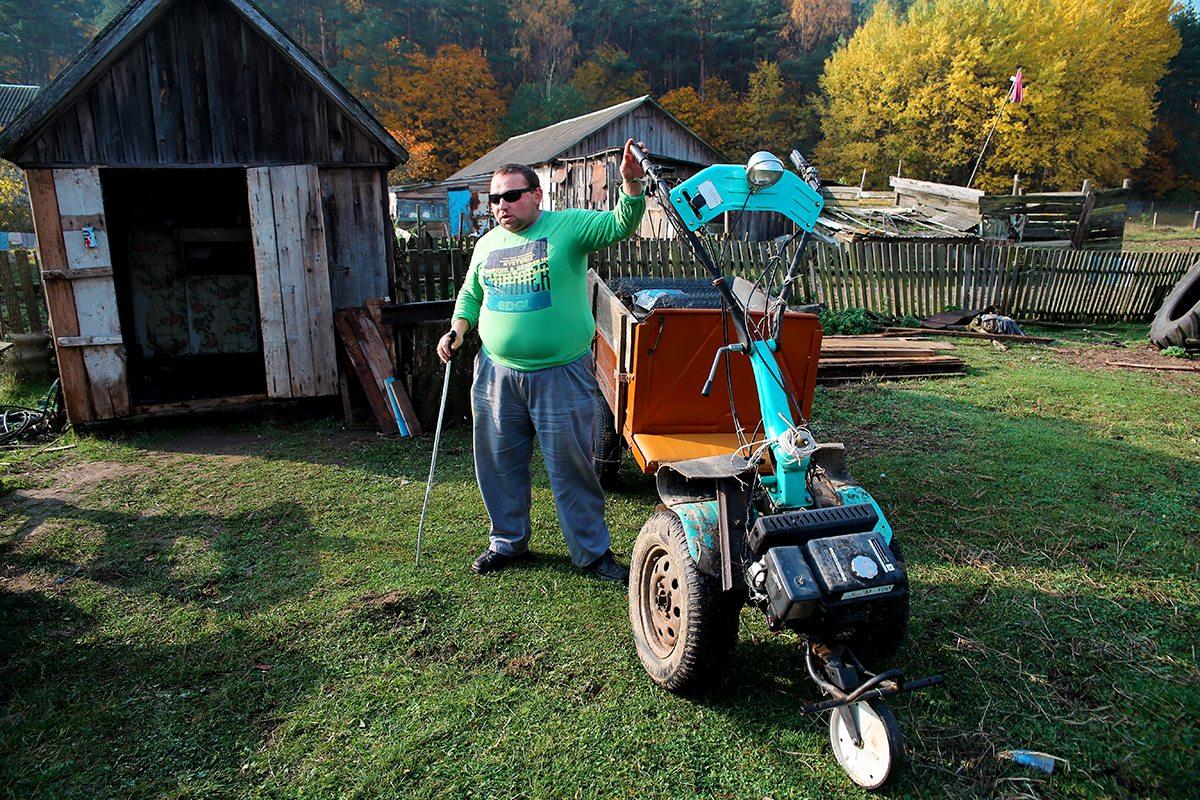 Анатолий управляется по хозяйству, используя технику.