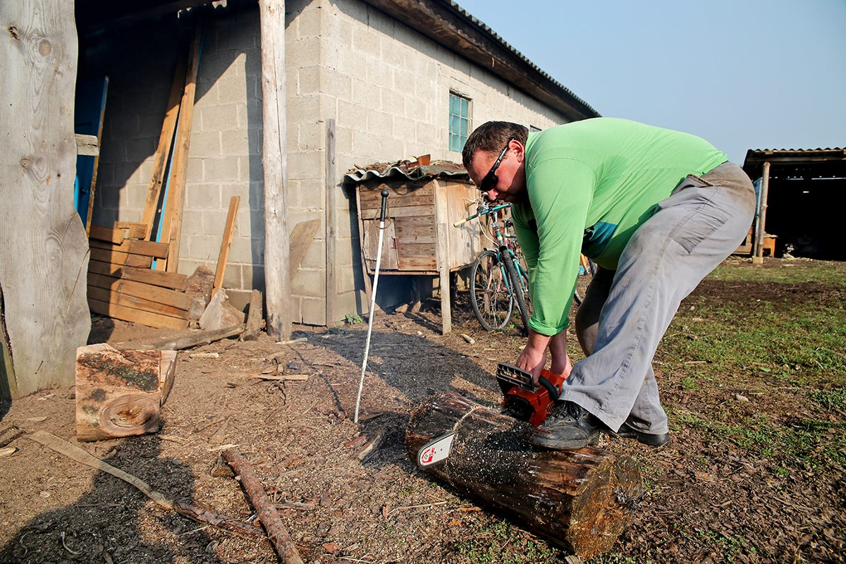 Мужчина пилит дрова бензопилой.