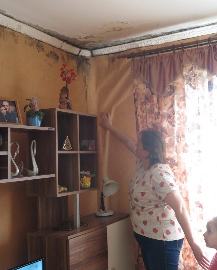 Татьяна Блашко показывает почерневшие от влаги потолок и стены в ее квартире. Фото: Евгений ТИХАНОВИЧ