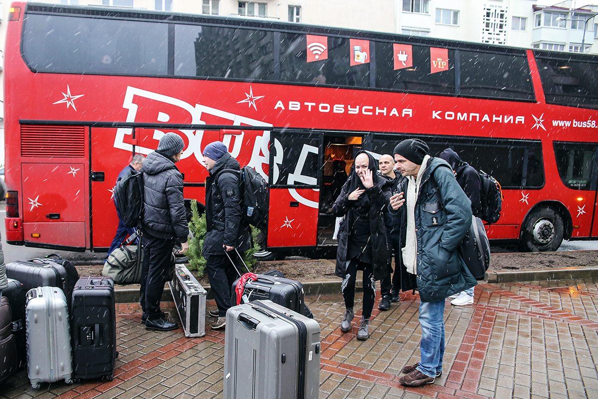 Участники группы ДДТ выгружают вещи из автобуса.