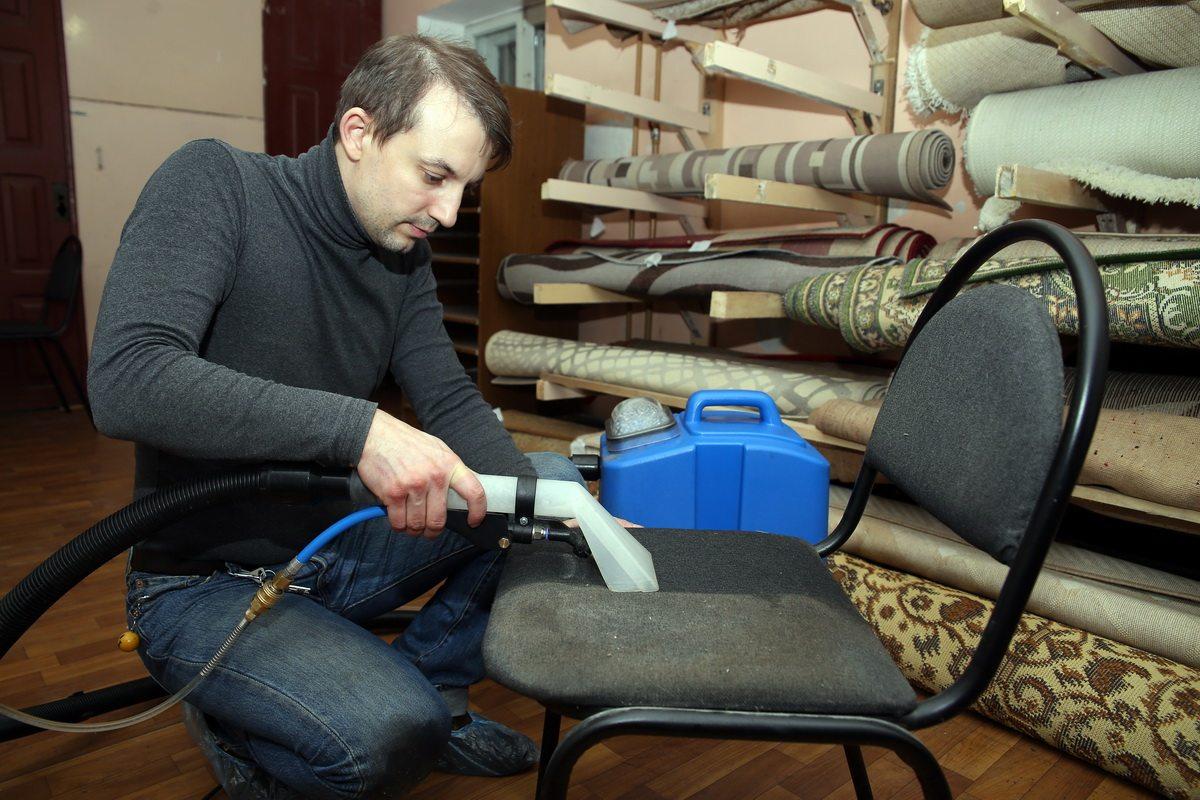 Сотрудник фирмы Василий Свириденко очищает офисный стул с помощью профессионального экстрактора для чистки мягкой мебели и ковров. фото: Евгений ТИХАНОВИЧ
