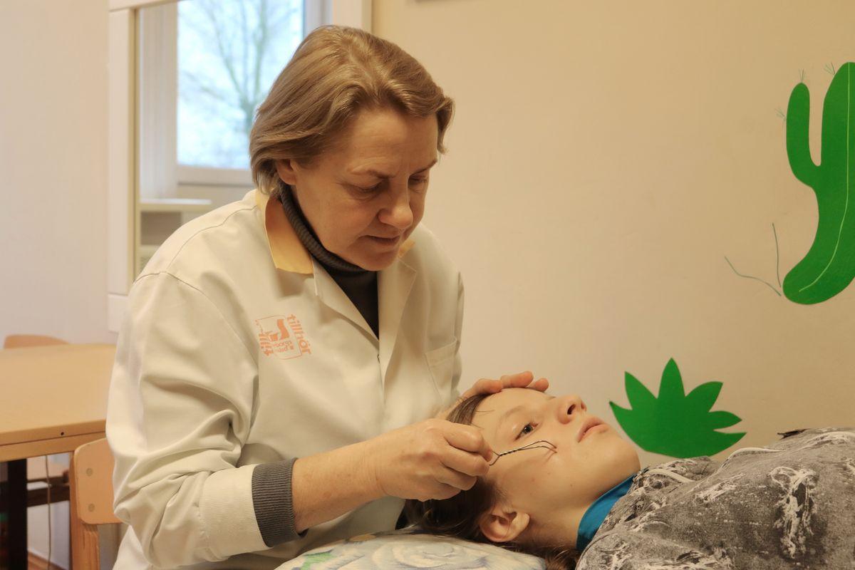 Учитель-логопед Елена Рубан проводит сеанс логопедического массажа.