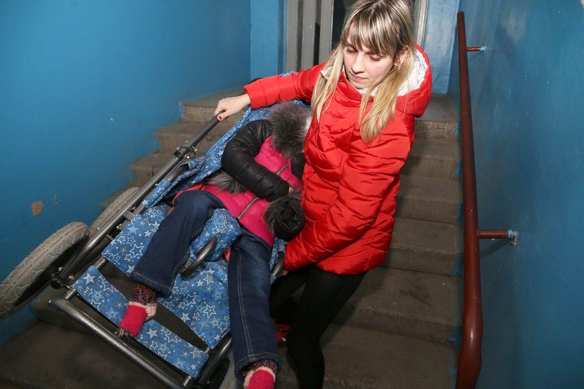 Чтобы отправится на прогулку с  дочерью Юле Левашовой приходится нести коляску с ребенком. Фото: Евгений ТИХАНОВИЧ
