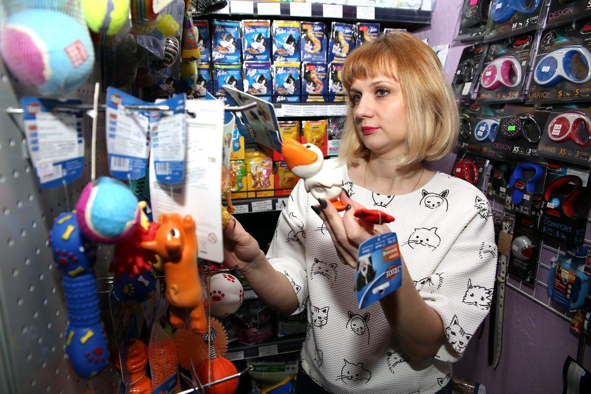 Владелица зоомагазина Елена Якубович выбирает покупателю игрушку для собаки.  Фото: Евгений  ТИХАНОВИЧ