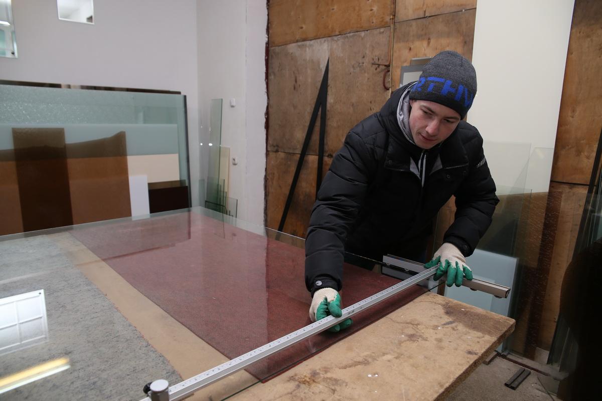 Евгений Барсукевич производит замеры, чтобы вырезать стекло нужного размера. Фото: Евгений ТИХАНОВИЧ
