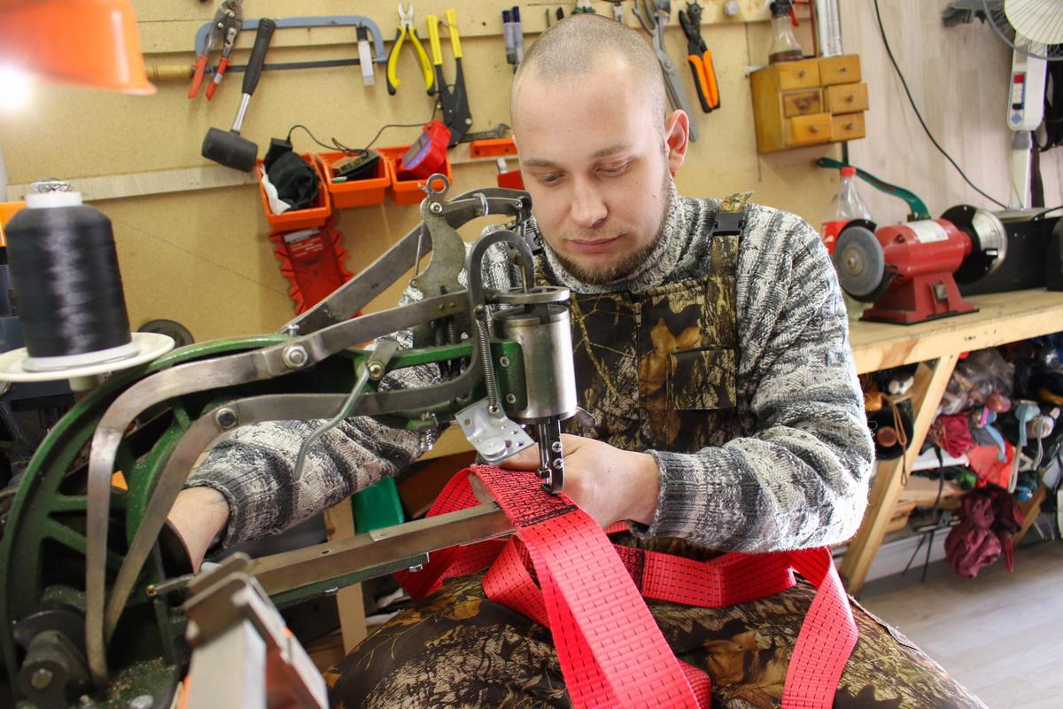 Максим Давиденко на обувной швейной машине прошивает разорванный тросс для буксировки авто. Фото: Александр ЧЕРНЫЙ