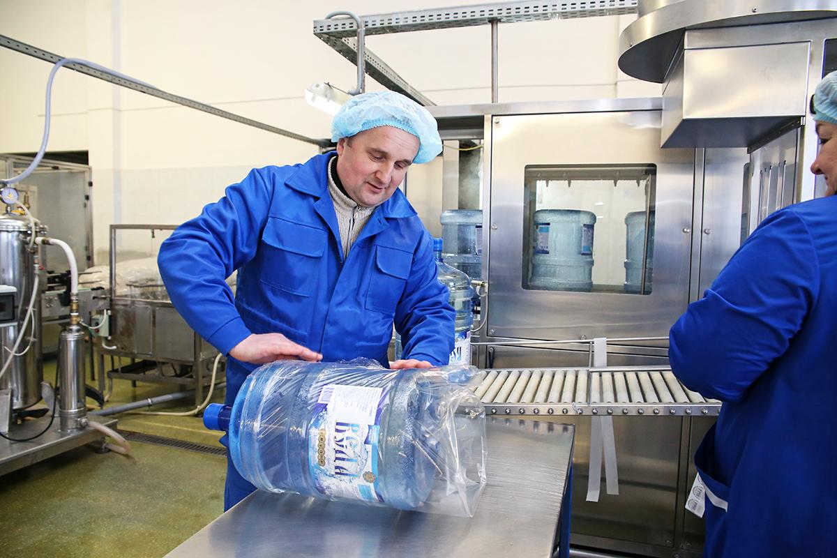 Машинист РУМ участка розлива Владимир Ахрем упаковывает бутылки перед отправкой на склад.