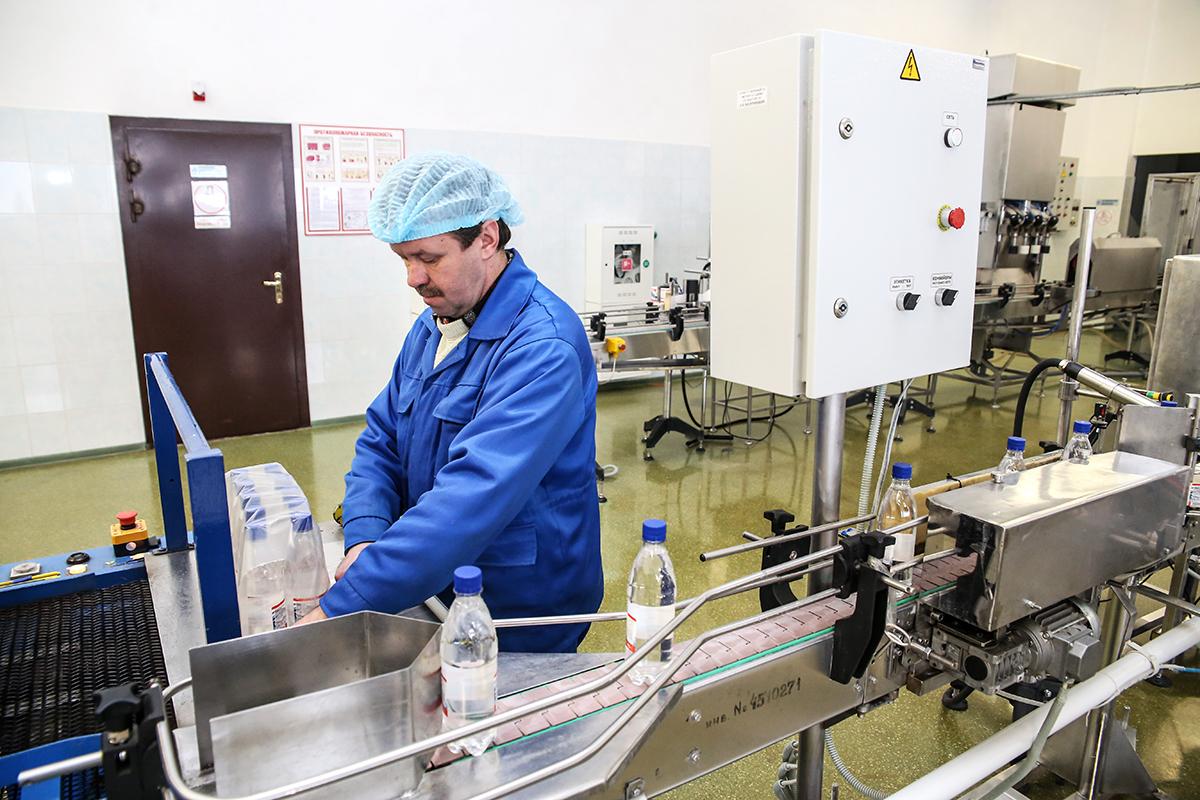 """Машинист РУМ участка розлива воды """"Веда"""" Сергей Черномаз упаковывает бутылки, которые сходят с конвейера."""