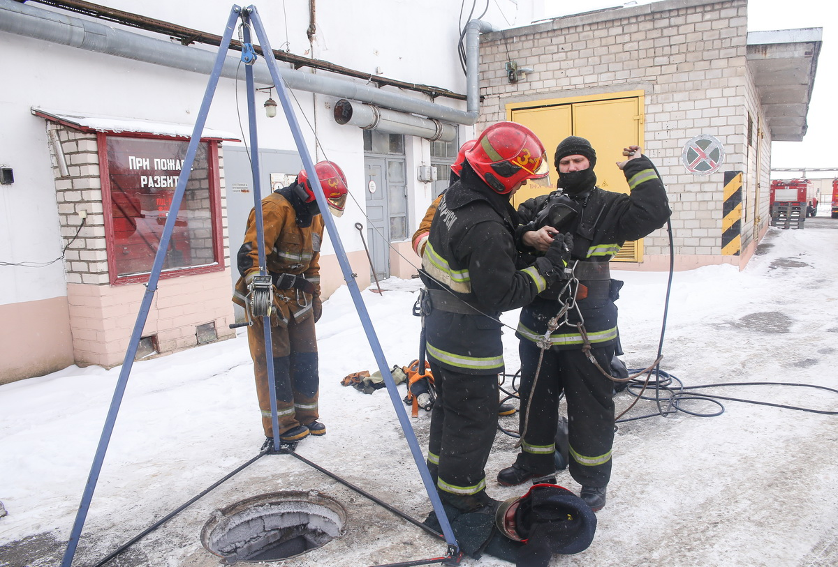 Подготовка спасателя к спуску в канализационный колодец за пострадавшим.
