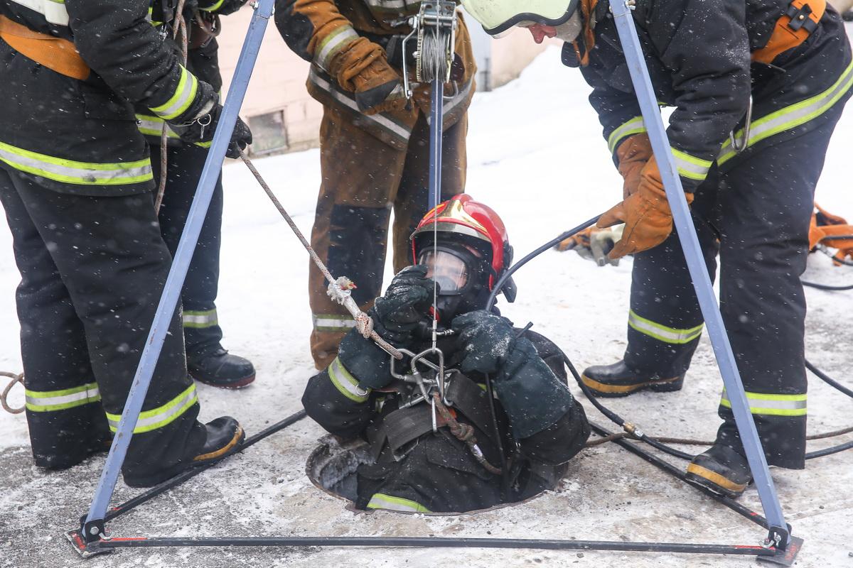 Спуск спасателя за пострадавшим в канализационный колодец.