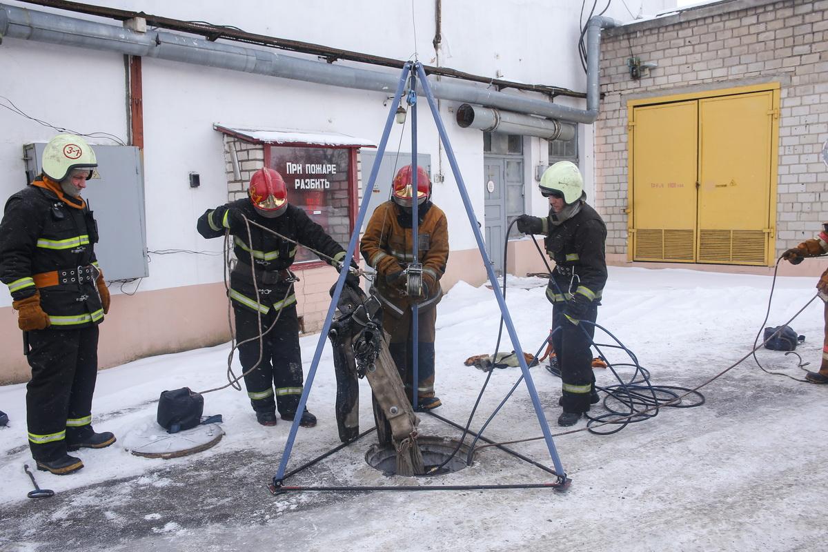 Спасатели достают пострадавшего (макет) из канализационного колодца.
