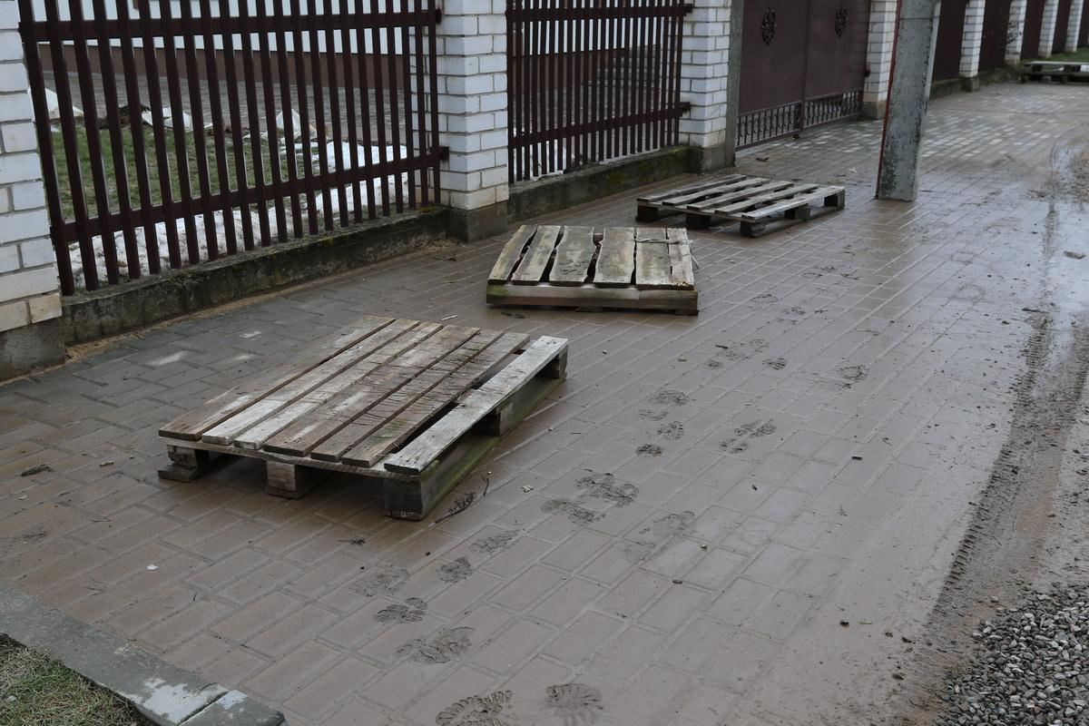 Деревянные поддоны остались на улице после «потопа», который был в 4-м переулке Славянском в понедельник, 12 марта. Людям приходится ходить по поддонам, чтобы пройти к своему дому.