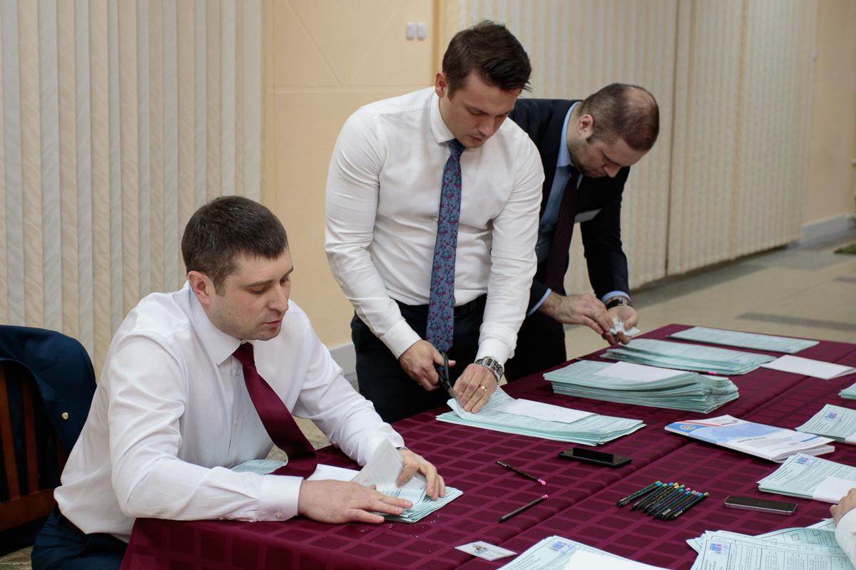 """Члены избирательной комиссии """"гасят"""" неиспользованные бюллетени."""