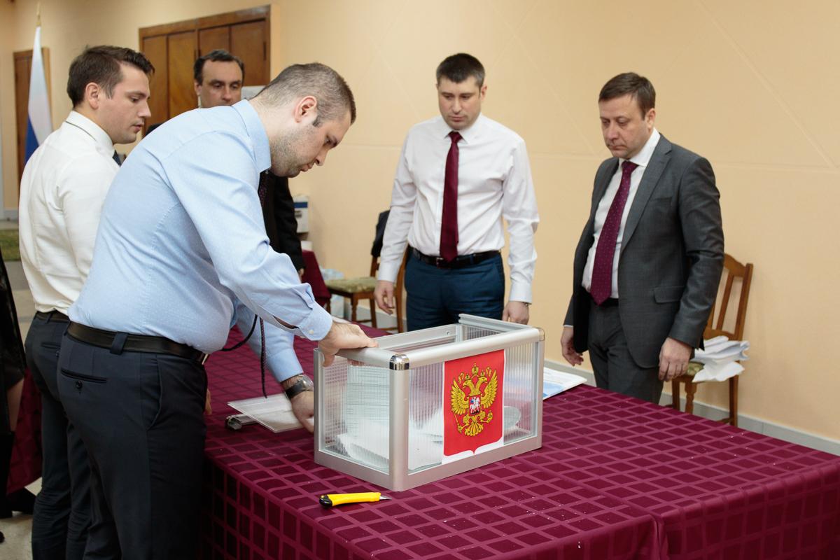Избирательная комиссия вскрывает переносной ящик для голосования.
