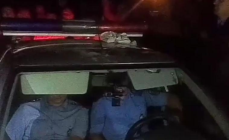 Скриншот с закрытого видео о конфликте в Ольшанах. На видео видно, как автомобиль ГАИ обступили местные жители. Инспекторы сидят в салоне служебного автомобиля, tut.by