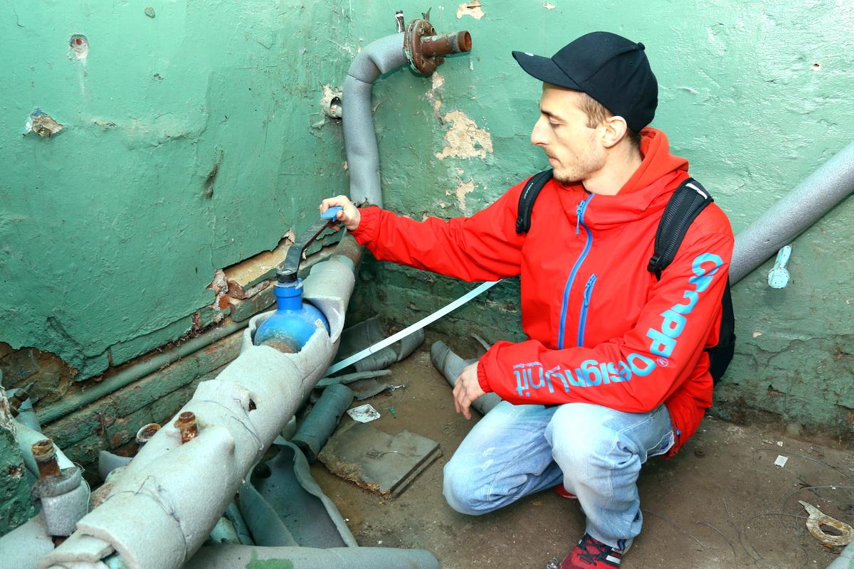 Антон Манько в теплопункте купленного здания показывает трубы, которые раньше были присоединены к исчезнувшему бойлеру.  Фото: Александр ЧЕРНЫЙ