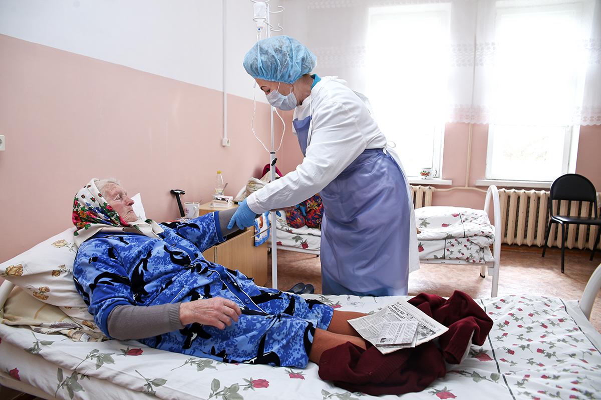 Процедурная медсестра Раиса Булак оказывает помощь 79-летней Ларисе Иосифовне.   Фото: Евгений ТИХАНОВИЧ