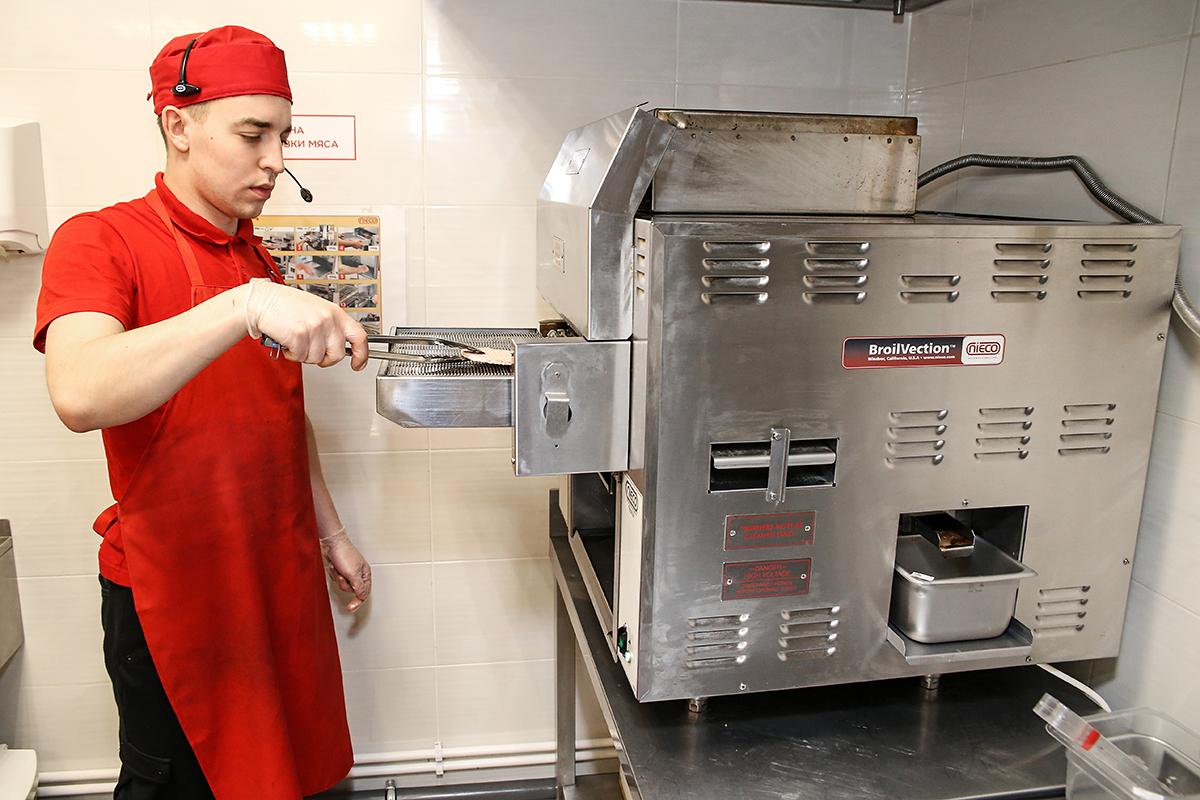 Говяжьи котлеты готовят на гриле. Все оборудование в ресторане американского производства.