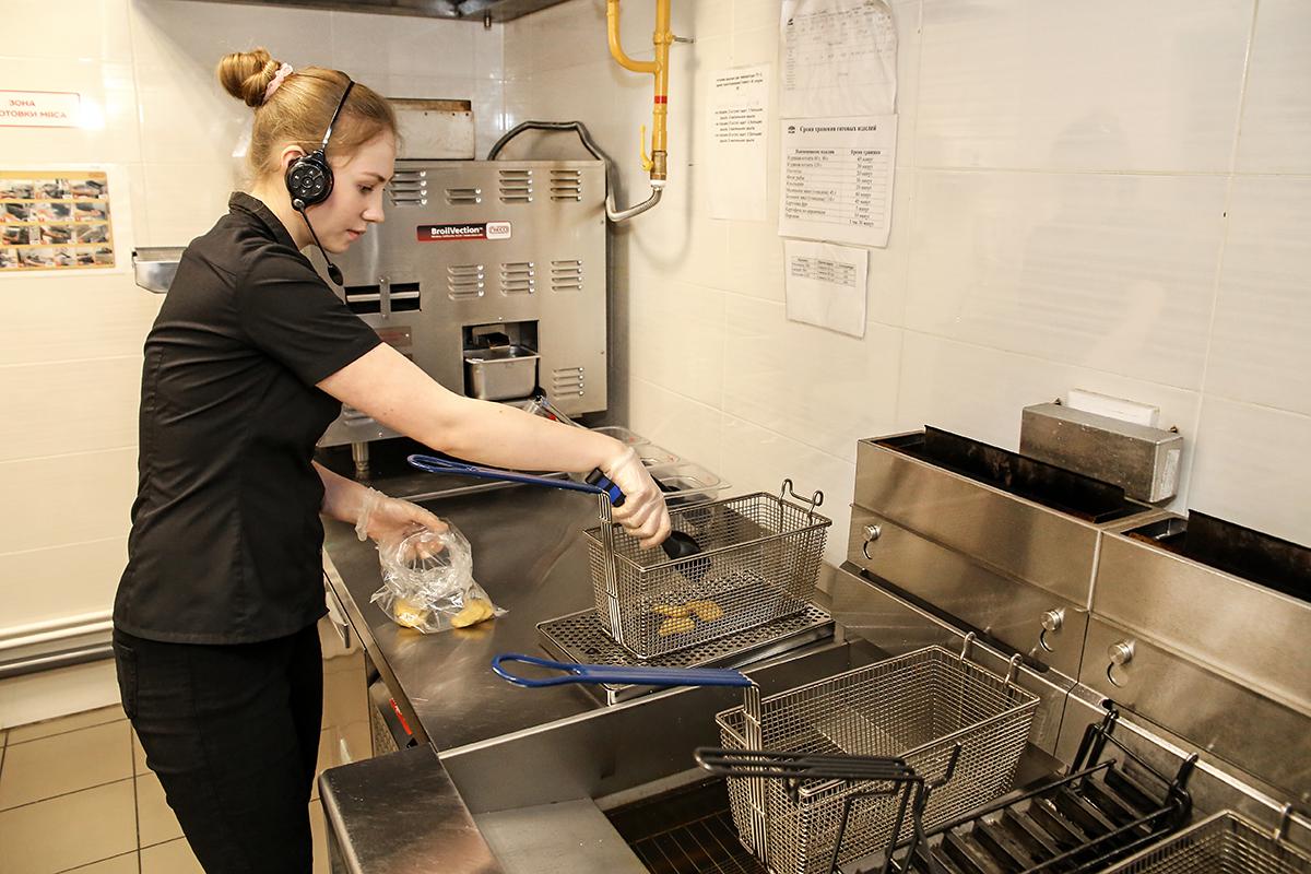 Сотрудник ресторана Оксана Очповская кладет куриные наггетсы для жарки во фритюре.