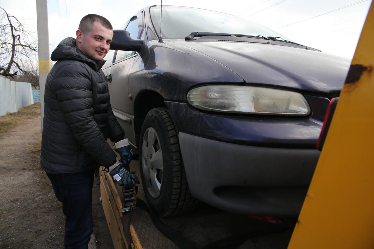 Кирилл Казанцев закрепляет неисправный автомобиль на платформе эвакуатора.  Фото: Евгений ТИХАНОВИЧ