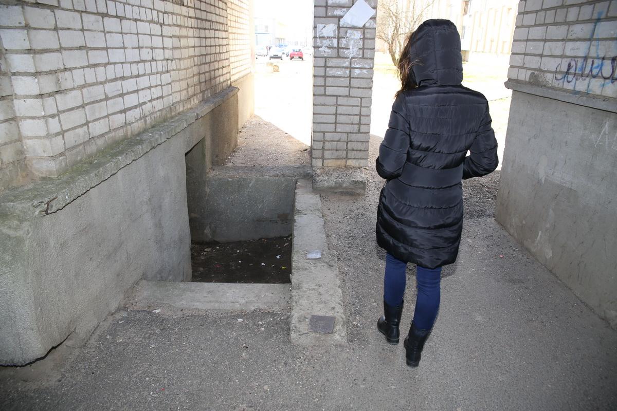 Даша у входа в подвал на улице Жукова, 16/1, куда она провалилась, получила травмы. Девушка стесняется своего разбитого лица, поэтому согласилась фотографироваться только со спины. Фото: Eвгений ТИХАНОВИЧ